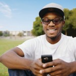 African American man in park using cell phone